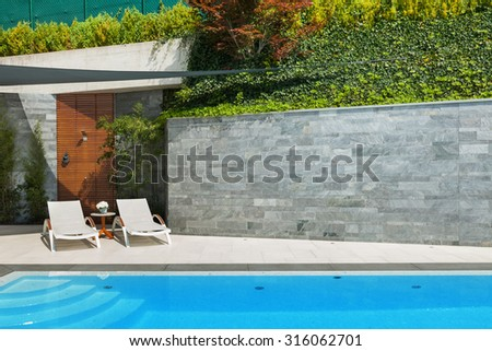 beautiful house, sunbeds view from the poolside, summer day - stock photo