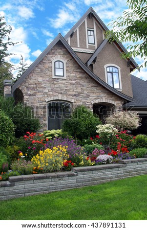 Beautiful house surrounded by a colorful perennial flower garden.
