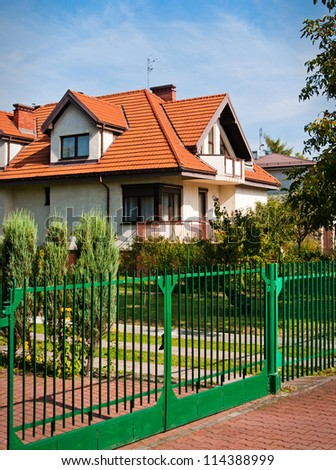 beautiful house with a green fence - stock photo