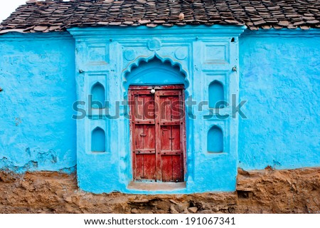Beautiful house with blue color walls built in traditional Indian rustic style, Madhya Pradesh state, India. - stock photo