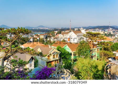 Beautiful houses with tile roofs in the Da Lat city (Dalat) on the blue sky background in Vietnam. Da Lat and the surrounding area is a popular tourist destination of Asia. - stock photo