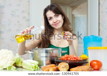 beautiful housewife cook vegetables with oil at her kitchen at home - stock photo