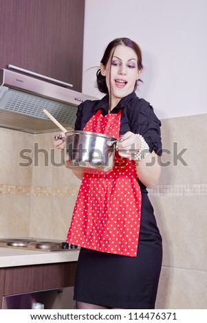 Beautiful housewife holding a pan - stock photo