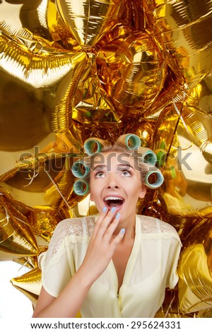 Beautiful housewife is surrounded by golden balloons. She is looking at them up with shock. She is raising her hand to wide open mouth - stock photo