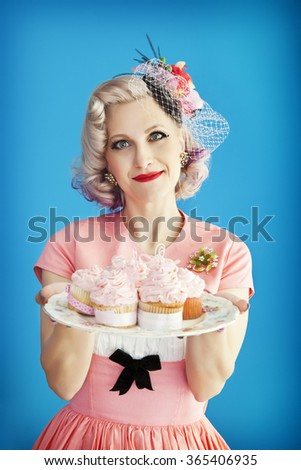 Beautiful, housewife & Mom dressed in fabulous vintage attire, holding a plate of homemade cupcakes. - stock photo