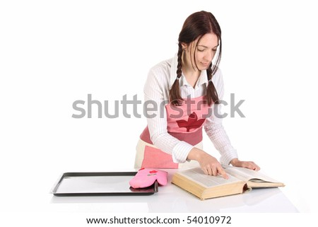 beautiful housewife preparing and reading with a book recipe - stock photo