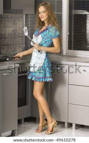 beautiful housewife with hot frying pan in the kitchen