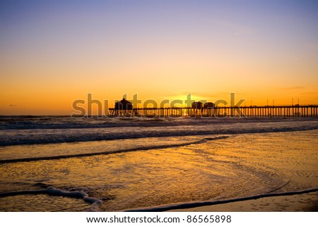 Beautiful hue of blue and yellow and orange sunset at Huntington beach pier - stock photo
