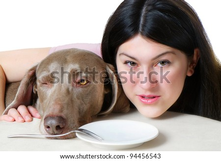 Beautiful hungry young woman and dog - stock photo