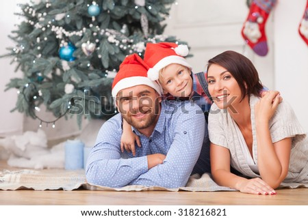 Beautiful husband and wife are lying on flooring near Christmas tree. Their son is embracing them with joy. They are smiling happily - stock photo