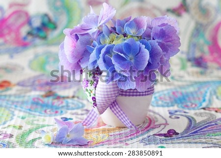 beautiful hydrangea flowers in a pot decorated with a heart on a beautiful tablecloth. - stock photo