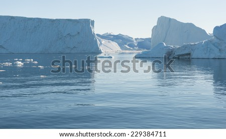 Beautiful Icebergs in Greenland with blue Sky - stock photo
