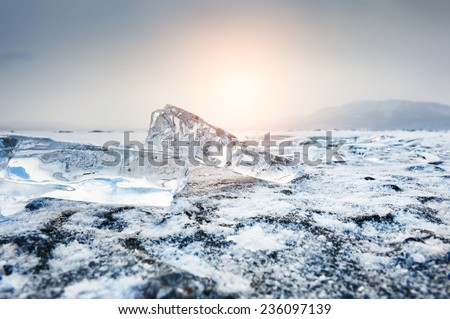 Beautiful icicles at sunset. Winter landscape with ice on the lake. Small depth of sharpness. Creative toning effect - stock photo