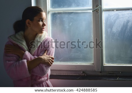 Beautiful ill sad cancer patient girl in pajamas  looking through hospital window. - stock photo