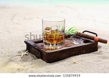 Beautiful image of scotch on the rocks in a classy wooden tray on a sandy beach. - stock photo