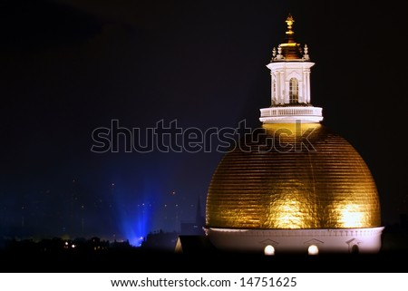 beautiful image of the golden dome of the massachusetts state house at night with a blue glow rising from the charles river
