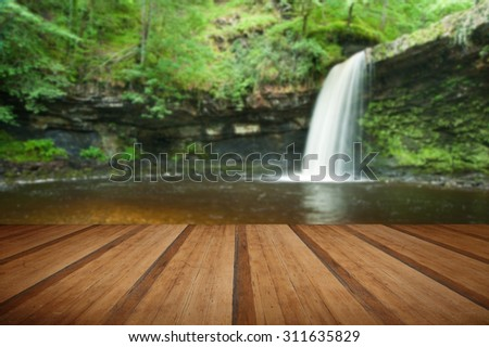Beautiful image of waterfall in forest with stream and lush green foliage with wooden planks floor - stock photo