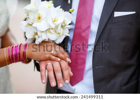 Beautiful indian bride and caucasian groom, after wedding ceremony. hands of man and woman with rings and traditional indian jewelry - stock photo