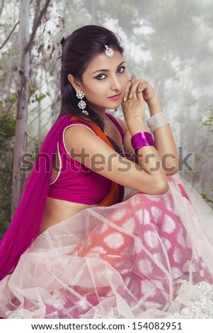 Beautiful Indian bride in colorful dress on forrest background. - stock photo