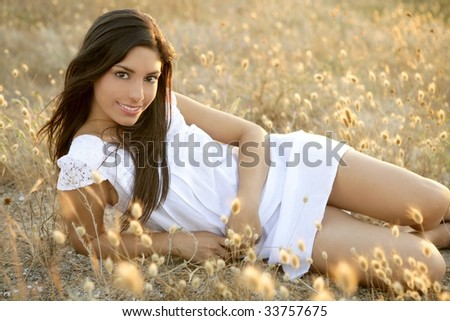 Beautiful indian brunette having a rest on a golden summer field - stock photo