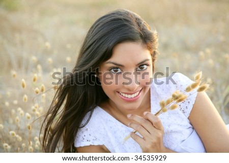 Beautiful indian brunette having a rest on a golden summer field