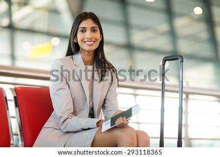 beautiful indian business woman waiting for her flight at airport - stock photo