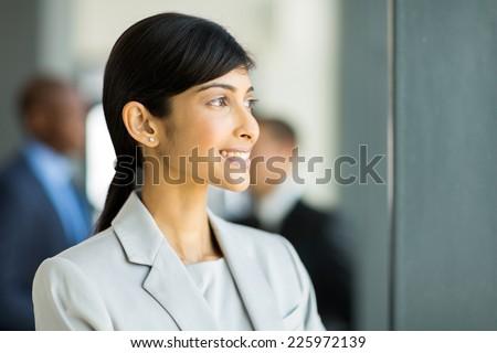 beautiful indian businesswoman looking outside office window - stock photo