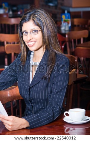 beautiful indian businesswoman reading financial newspaper