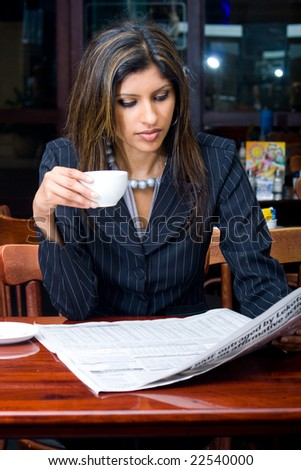beautiful indian businesswoman reading financial newspaper and drinking coffee in a cafe - stock photo