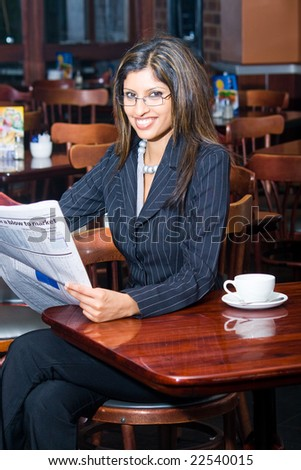 beautiful indian businesswoman reading financial newspaper in a cafe