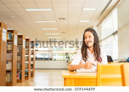 beautiful indian college girl reading a book in library (with selective focus and tone adjustment) - stock photo