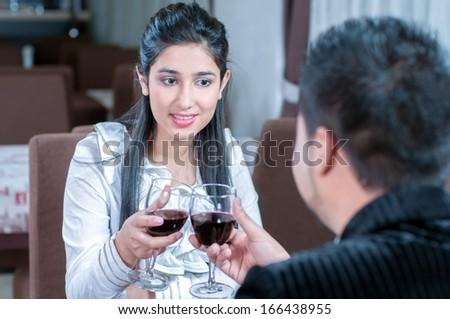 beautiful indian couple with wine glass. Having romantic talk - stock photo