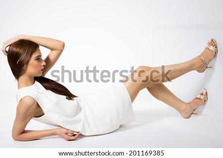 beautiful Indian fashion model sitting on the floor and posing, Indian fashion model wearing white outfit and posing for camera. - stock photo