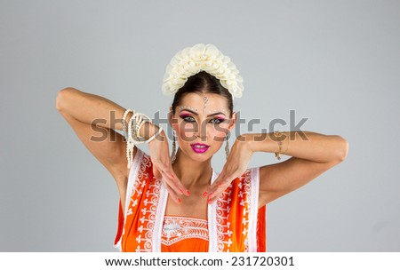 Beautiful Indian girl dancing in national dress - stock photo