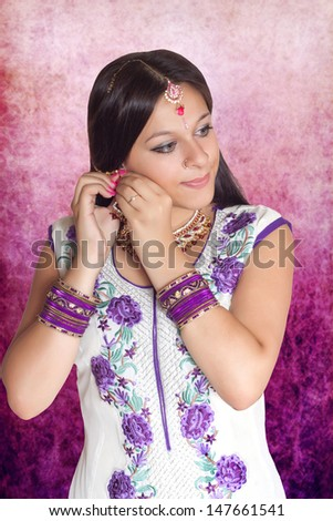 Indian girl in traditional indian clothing on purple background