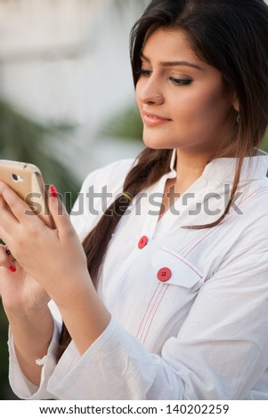 beautiful Indian girl using mobile phone, girl sending or receiving sms - stock photo