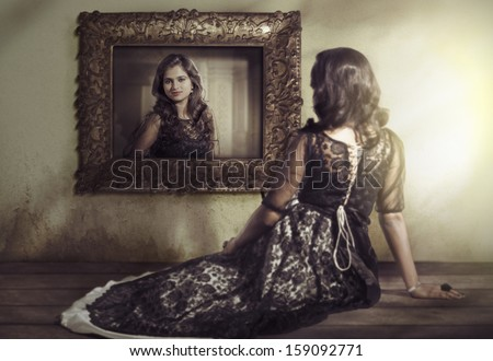 Beautiful Indian girl wearing black gown sitting and looking at the mirror. - stock photo