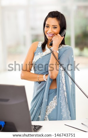 beautiful indian office worker talking on the phone - stock photo
