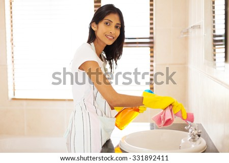 beautiful indian woman cleaning bathroom sink - stock photo