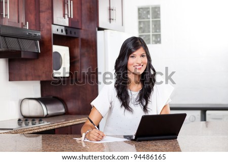 beautiful indian woman doing home finance in kitchen