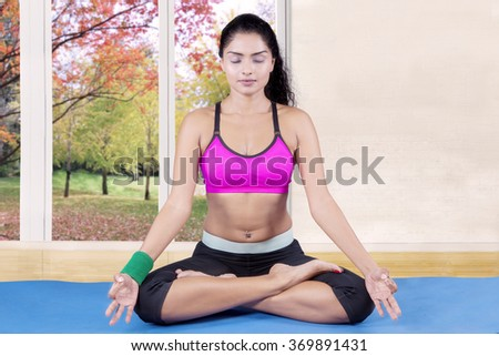 Beautiful indian woman doing meditation on the mattress at home with autumn background on the window - stock photo