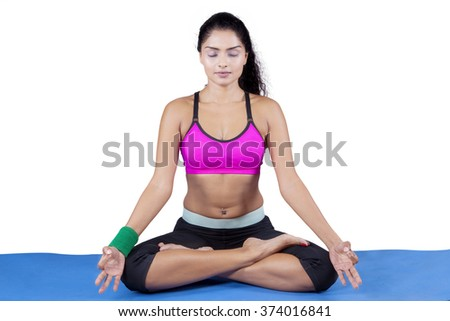 Beautiful indian woman doing meditation while wearing sportswear and sitting on the mattress, isolated on white background - stock photo