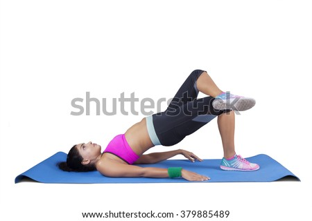 Beautiful indian woman doing yoga pose while wearing sportswear on the mattress, isolated on white background - stock photo
