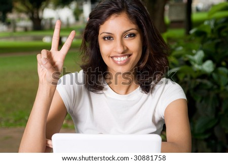 beautiful indian woman giving peace sign - stock photo