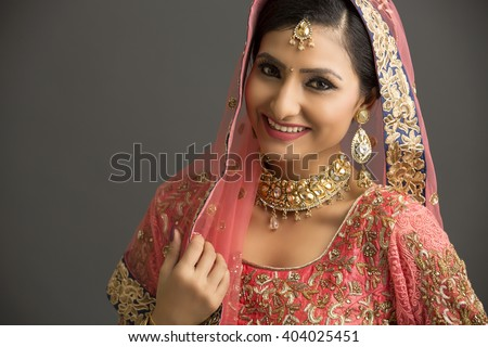 Beautiful Indian woman in glamorous outfit and jewelry with makeup in dark background. - stock photo
