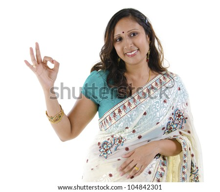 Beautiful Indian woman showing okay hand sign on white background - stock photo