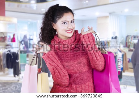Beautiful indian woman smiling at the camera while carrying shopping bags in the shopping center and wearing winter clothes - stock photo