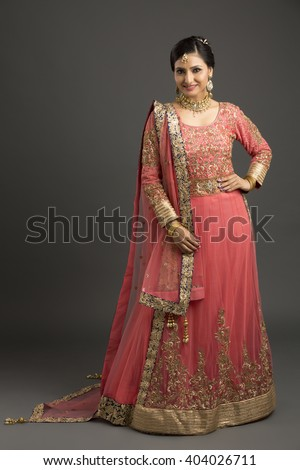 Beautiful Indian woman standing with glamorous outfit and jewelry with makeup in dark background. - stock photo