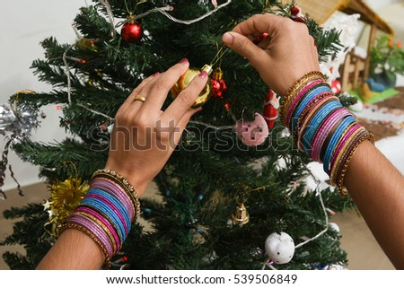 Beautiful Indian women hands wearing colorful bangles decorating Christmas tree with gifts and baubles. Rajasthani married woman wearing lot of ornaments hanging snowflakes on x'Mas day, North India.