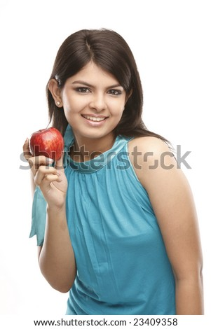 Beautiful Indian young woman with an apple against white background - stock photo